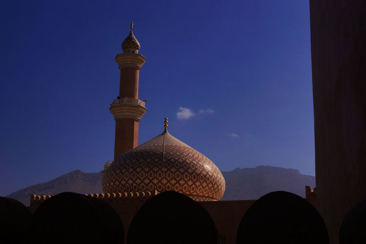 Low angle view of nizwa mosque blue sky