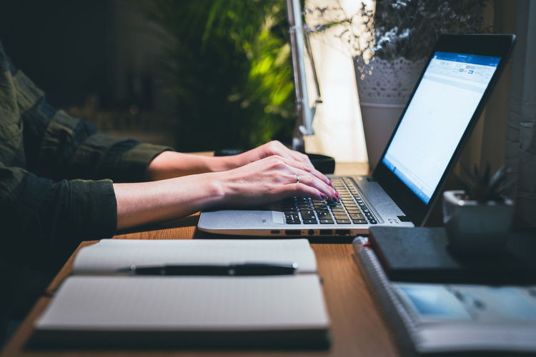 Woman hands typing on laptop on table. focus on hands typing. work from home concept