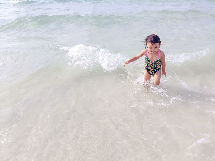 Children playing the sea happily, the concept of tourism. Ankle Deep In Water Beach Beauty In Nature Childhood Day Elementary Age Full Length Girls Leisure Activity Lifestyles Motion Nature One Person Outdoors People Real People Sea Standing Vacations Water Wave Young Adult