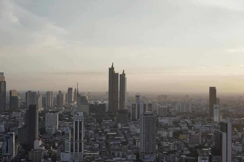 Aerial view of buildings in city against cloudy sky