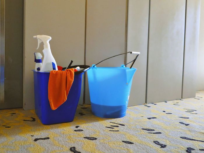 Close-up of buckets on carpet at home