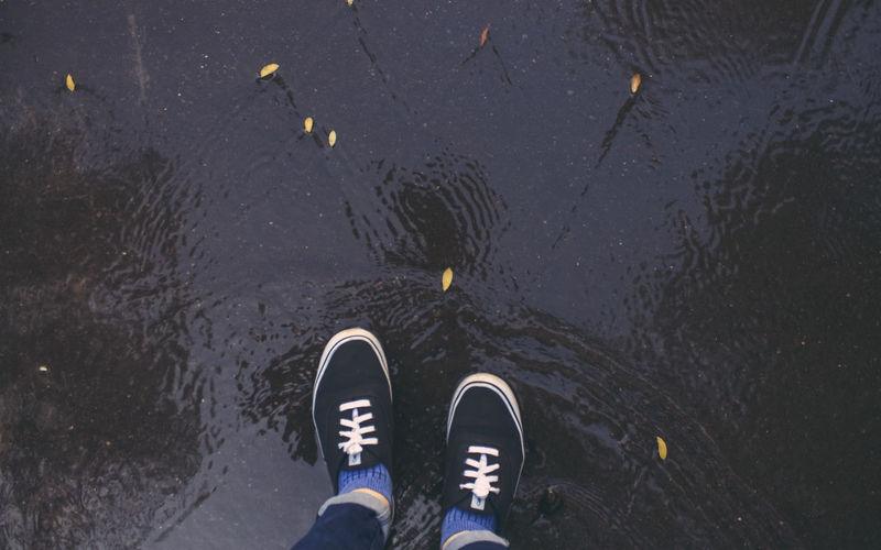 Low section of person standing on puddle during monsoon