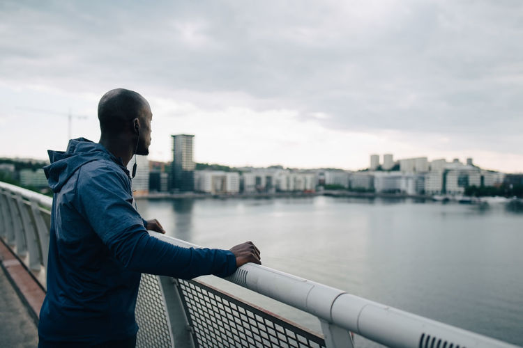 Man standing on railing by river against sky in city