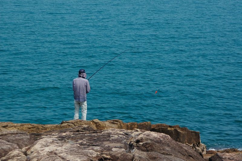 Rear View Of Man Fishing At Sea