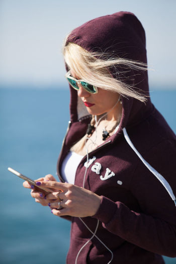 Blonde Blue Sky Casual Clothing Communication Day Girl Holding Leisure Activity Lifestyles Mobile Phone One Person Outdoors Portable Information Device Real People Sea Smart Phone Sunglasses Technology Using Phone Waist Up Water Wireless Technology Young Adult Young Woman Young Women