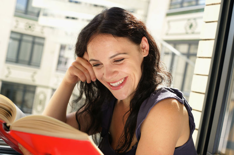 Portrait of smiling woman red book by window