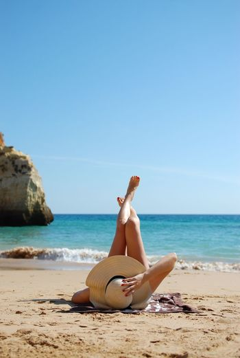 Woman sunbathing at beach against sky