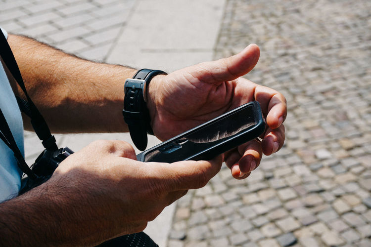 Midsection of man using mobile phone on street
