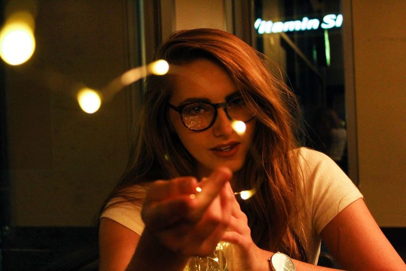 Playing with lights at Starbucks Lifestyles Young Women Illuminated Real People Young Adult Night Women Leisure Activity Beauty Nightlife Headshot Sitting Front View Holding Eyeglasses  Beautiful Woman Smiling One Person Indoors  Only Women Starbucks Canon Canonphotography Bokeh