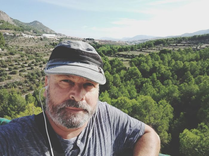 Portrait of man wearing cap listening music against landscape during sunny day