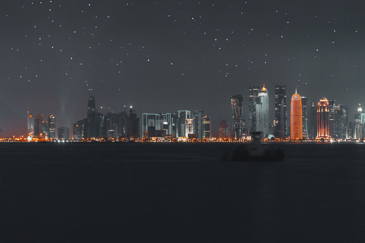 Illuminated buildings against star field in sky at night