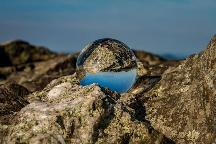 Close-up of glass globe on rock formation on land against sky