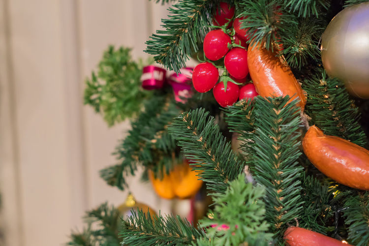 Christmas and new year  background. christmas tree with artificial sausagws, tomatoes and balls