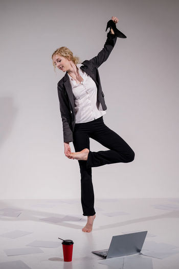 Full length of woman dancing against white background