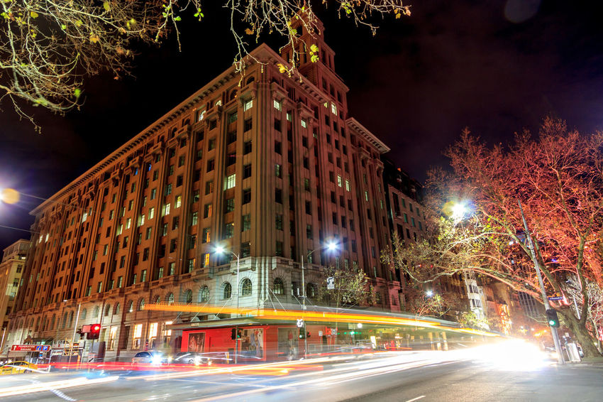 Cars and trams whizzing past the old T&G building on Bourke Street Architecture Blurred Motion Building Exterior Built Structure City City Street Illuminated Light Trail Long Exposure Mode Of Transportation Motion Nature Night No People Outdoors Plant Road Speed Street Transportation Tree