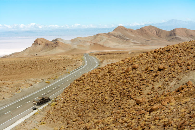 Scenic view of desert road against sky