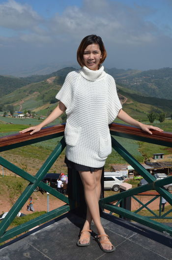 Portrait of smiling woman standing at observation point against sky