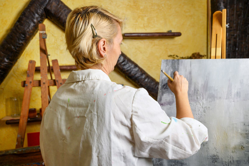 Rear view of painter painting at home
