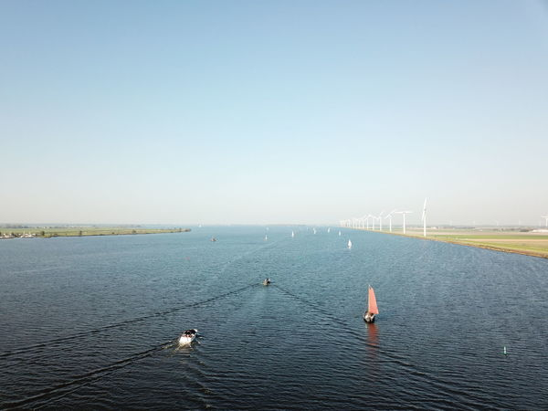 River from above Drone  Wind Turbine Beauty In Nature Boat Clear Sky Nautical Vessel Outdoors Renewable Energy Sailing Sea Sky Tranquil Scene Tranquility Transportation Water Waterfront