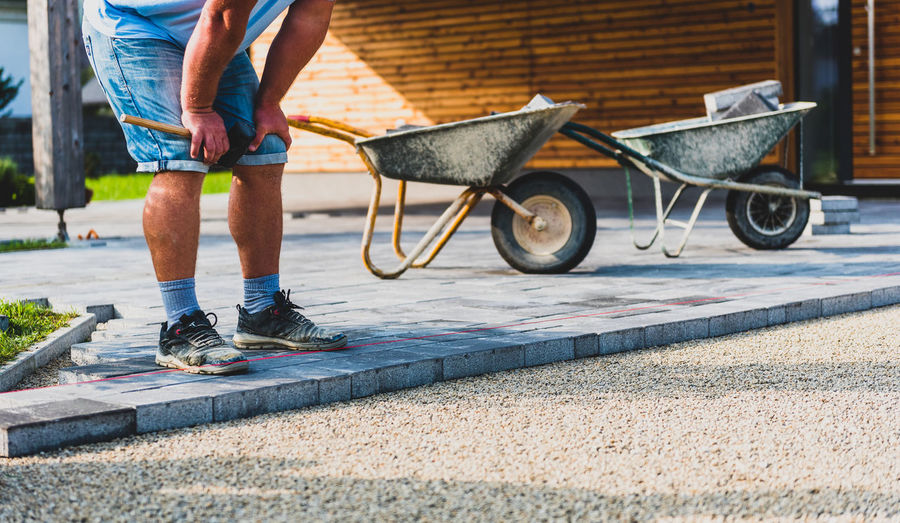 Low section of construction worker standing on paving stones