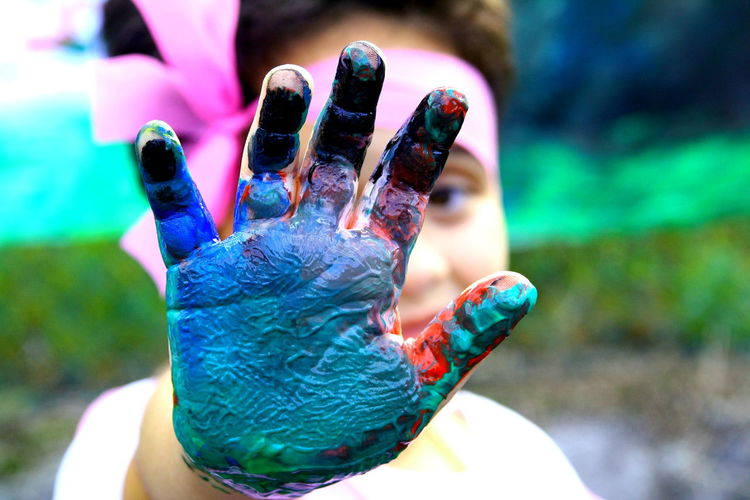 Cropped hand of girl with multi colored paint