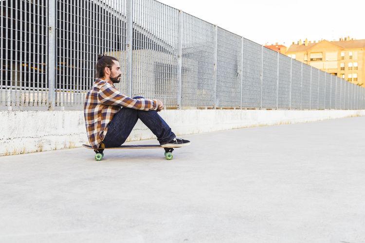 Man sitting on skateboard in city