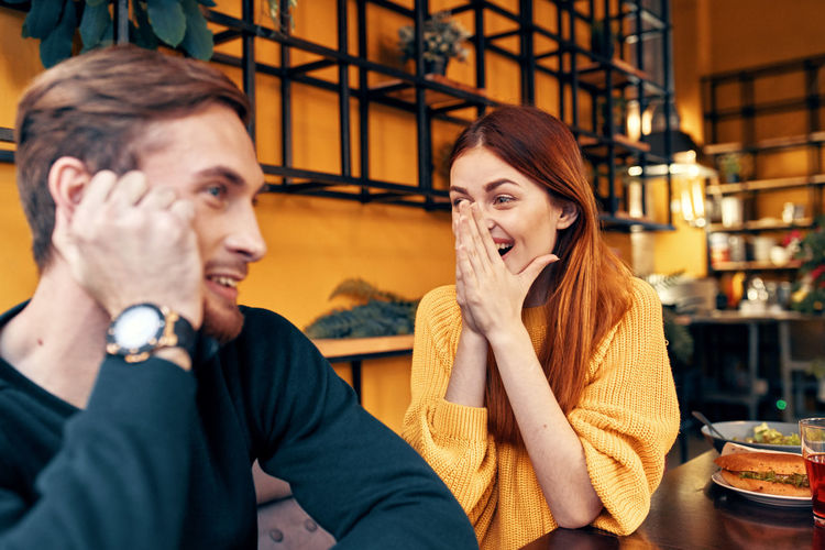 Portrait of young couple sitting in restaurant