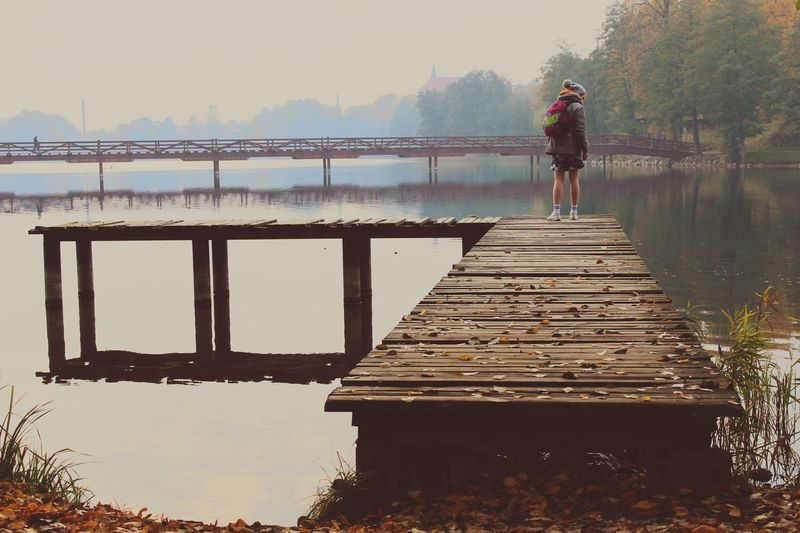 Woman standing on pier over lake