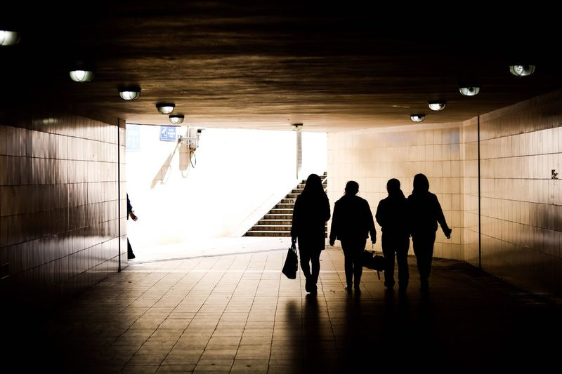 Rear view of silhouette women walking in illuminated tunnel