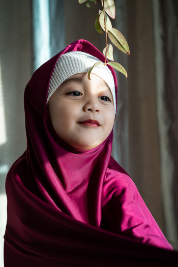 Portrait of a happy muslim toddler girl with hijab. natural light, selective focus.