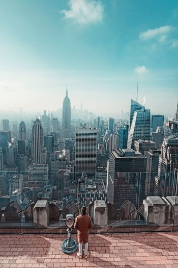 High Angle View Of Man Standing At Observation Point Against Cityscape