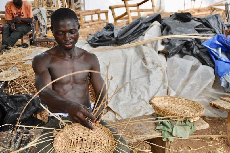 Shirtless man making wicker basket