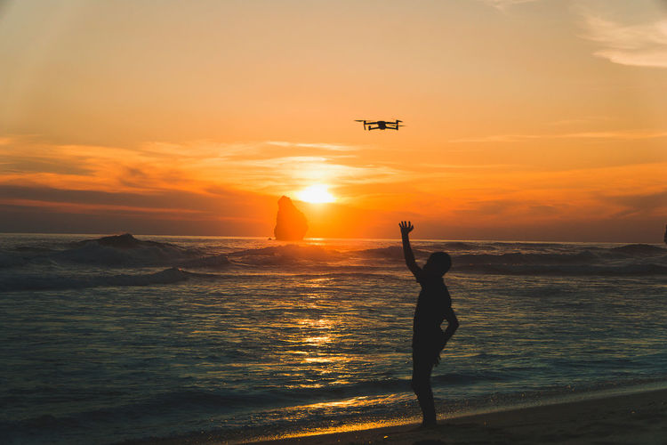 Silhouette person flying over sea against sky during sunset