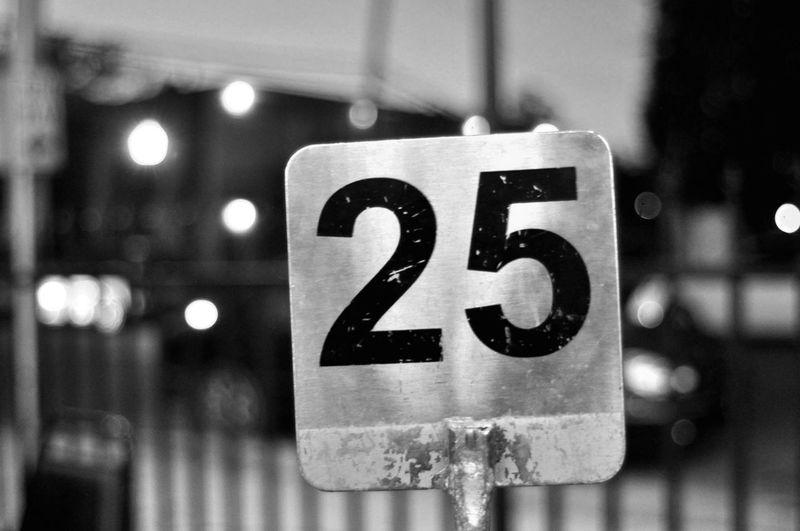 Close-Up Of Number 25 Against Defocused Lights At Night