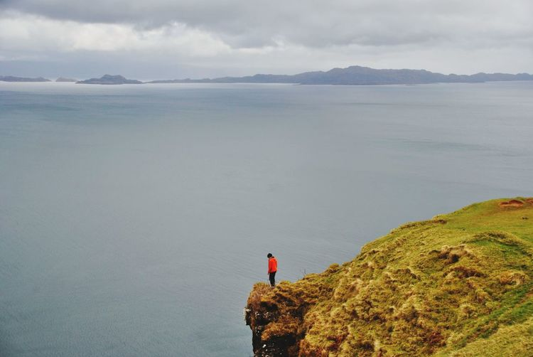 Rear view of man standing by sea on cliff