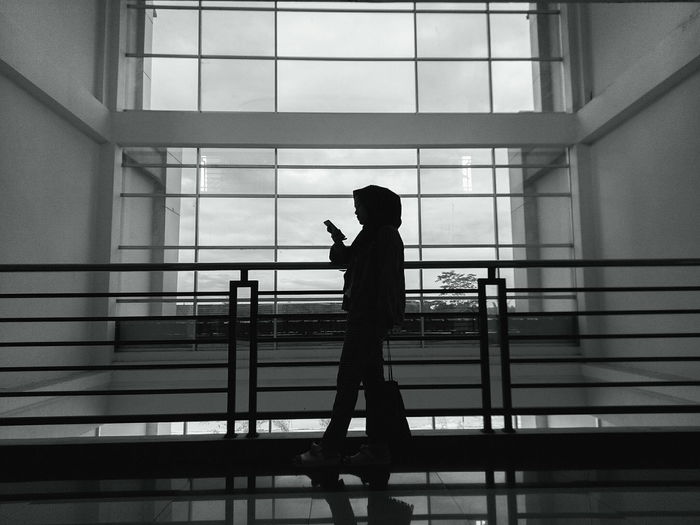 Side View Of Silhouette Woman Standing Against Railing In Building