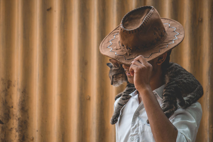 Teenage Boy Wearing Hat With Cat On Shoulder Against Corrugated Iron