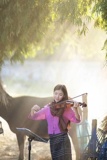 Portrait Of Young Woman Playing Violin By Horse