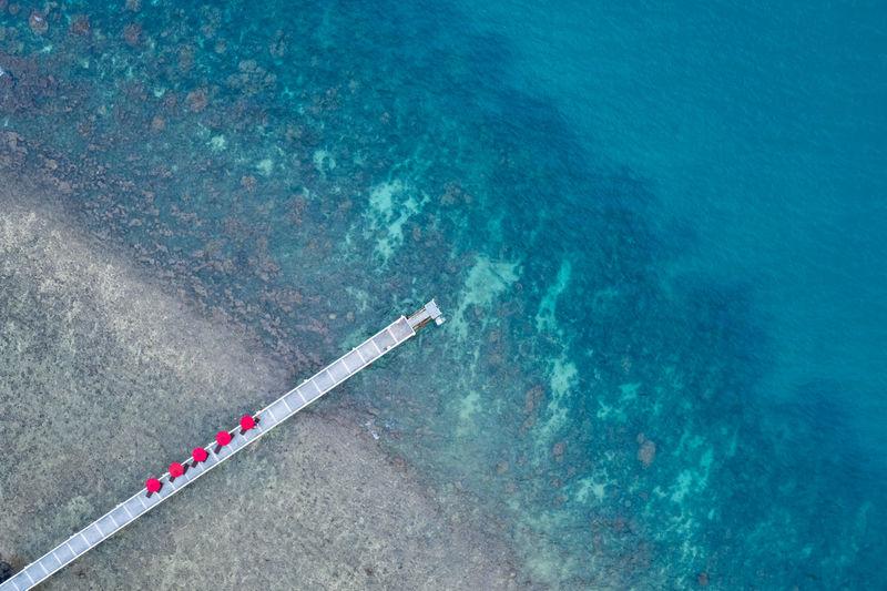 Bridge and red umbrella on the sea aerial view