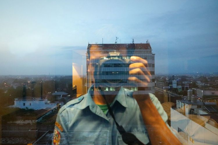 Digital composite image of man photographing cityscape