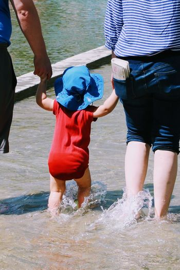 Water Togetherness Leisure Activity Family With One Child Bonding Outdoors Fun Child People Childhood Happiness Vacations Beach Summer Baby Toddler  Holding Hands Cute Unrecognizable People Backs Standing Splashing Walking Family Young Adult