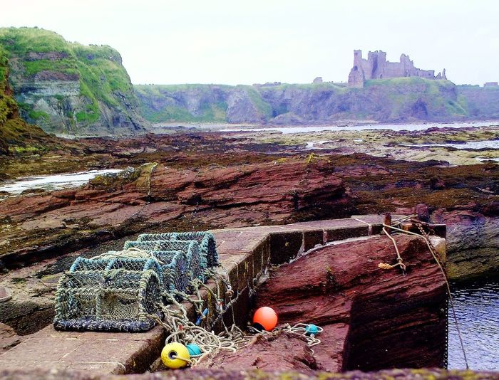 Lobster Traps On Wall Against Rocky Shore With Tantallon Castle In Background