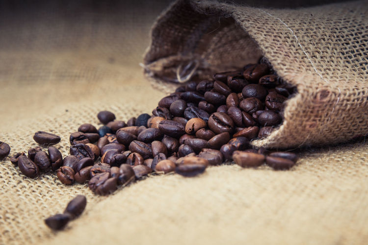 Roasted coffee beans spilling from sack