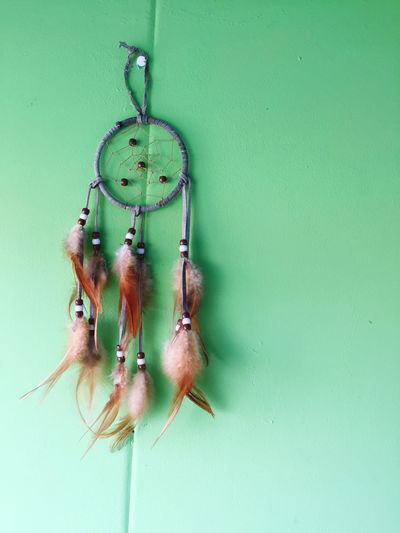 Low Angle View Of Dreamcatcher Hanging On Green Wall