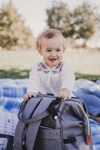 Cute baby girl sitting by bag on picnic blanket