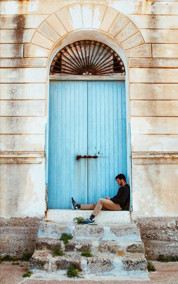 Man sitting in front of a closed door of an abandoned building at the beach