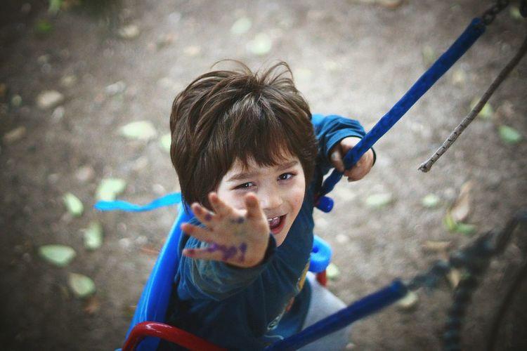 Portrait of boy enjoying swing in park