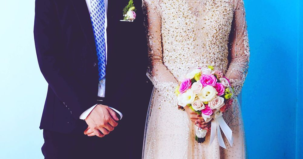 Midsection Of Well Dressed Couple Standing Against Wall During Wedding Ceremony