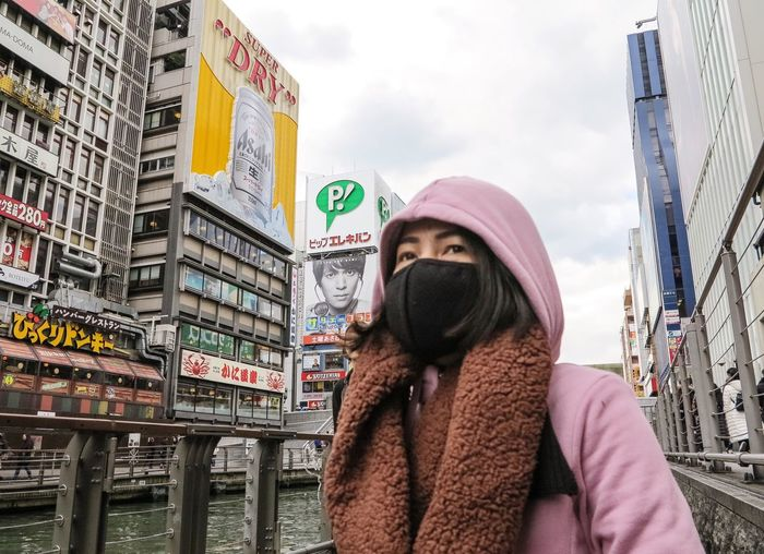 Low angle view of woman with covered face in city