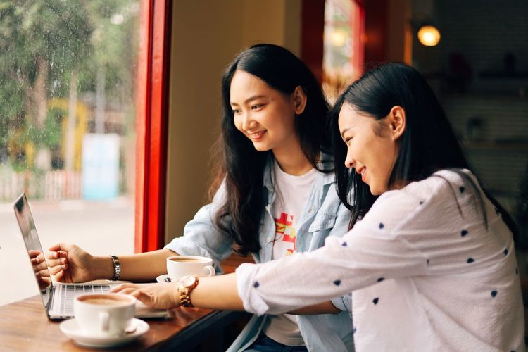 Two People Communication Wireless Technology Young Adult Women Young Women Drink Adult Cup Cafe Connection Lifestyles Technology Casual Clothing Food And Drink Mobile Phone Smiling Leisure Activity Real People Hair Outdoors